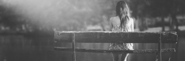 a girl sitting alone on a bench