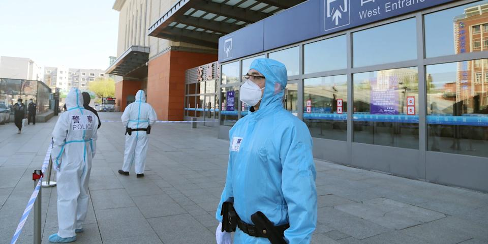 Police officers in protective suits in front a closed entrance to a train station, following the outbreak of the coronavirus in Jilin, Jilin province, China May 13, 2020.