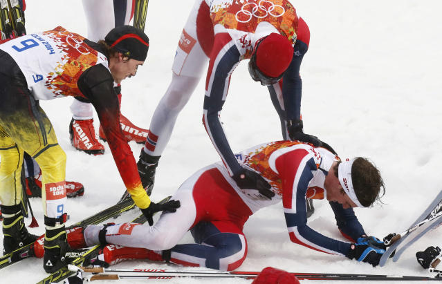 Norway's gold medal winner Joergen Graabak, right, is congratulated by Germany's bronze medal winner Fabian Riessle, left, and Norway's Magnus Hovdal Moan, top right, after the cross-country portion of the Nordic combined individual Gundersen large hill competition at the 2014 Winter Olympics, Tuesday, Feb. 18, 2014, in Krasnaya Polyana, Russia. (AP Photo/Dmitry Lovetsky)