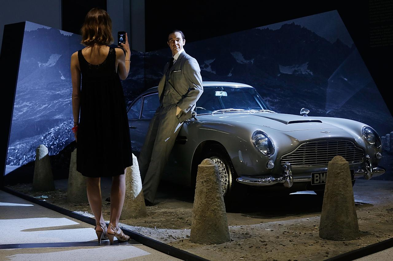 An employee of the Barbican poses in front of a Sean Connery waxwork and the famous Aston Martin DB5 at the Fifty Years of Bond Style press view on July 5, 2012 in London, England. The Barbican is celebrating the 50th anniversary of James Bond with an exhibition showcasing the inside story of the design and style of the iconic films.  (Photo by Matthew Lloyd/Getty Images)