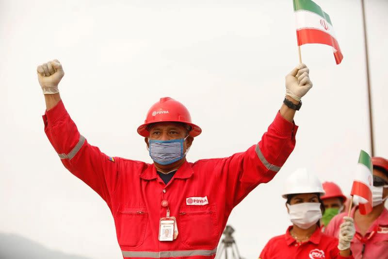 """FILE PHOTO: A worker of the state-oil company Pdvsa holds an Iranian flag during the arrival of the Iranian tanker ship """"Fortune"""" at El Palito refinery in Puerto Cabello"""