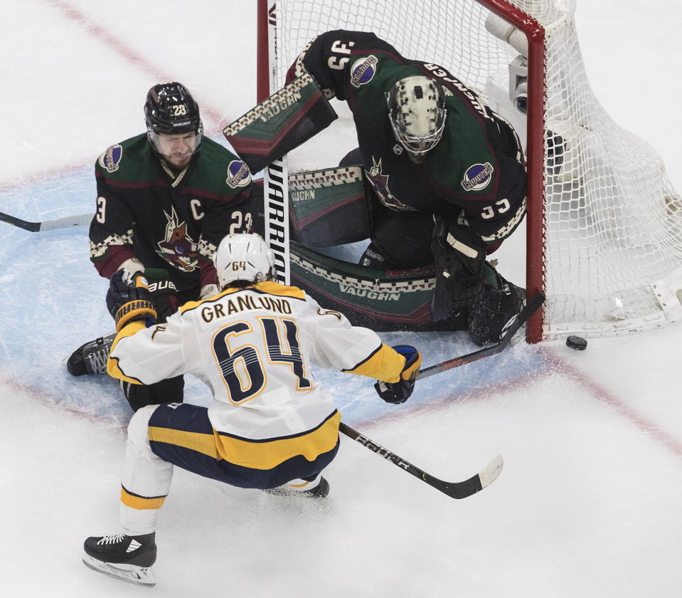 Nashville Predators' Mikael Granlund (64) is stopped by Arizona Coyotes goalie Darcy Kuemper (35) as Coyotes' Oliver Ekman-Larsson (23) defends during first period NHL hockey action in Edmonton, Alberta, Friday, Aug. 7, 2020. (Jason Franson/The Canadian Press via AP)