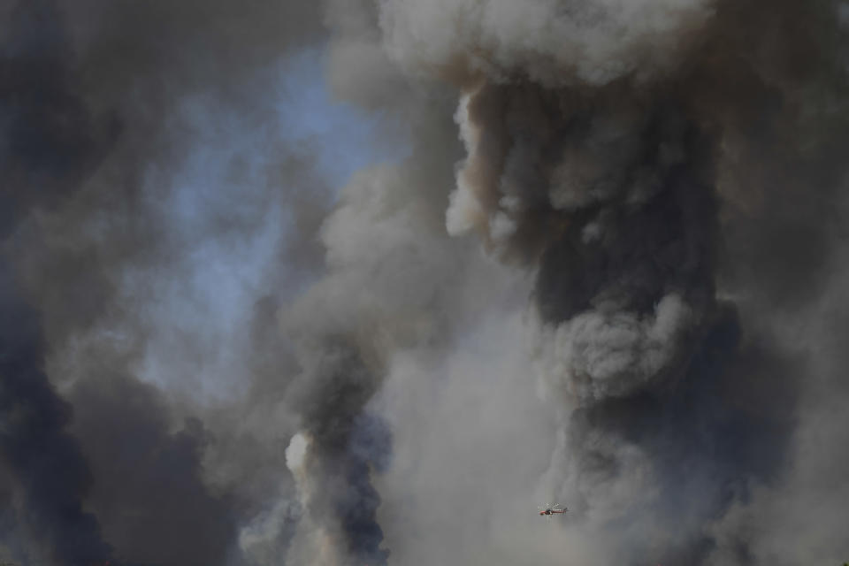 A helicopter of the Greek Fire Service flies during a wildfire that broke out in Tatoi, northern Athens, Greece, Tuesday, Aug. 3, 2021. The Greek Fire Service maintained an alert for most of the country Tuesday and Wednesday, while public and some private services shifted operating hours to allow for afternoon closures. (AP Photo/Michael Varaklas)