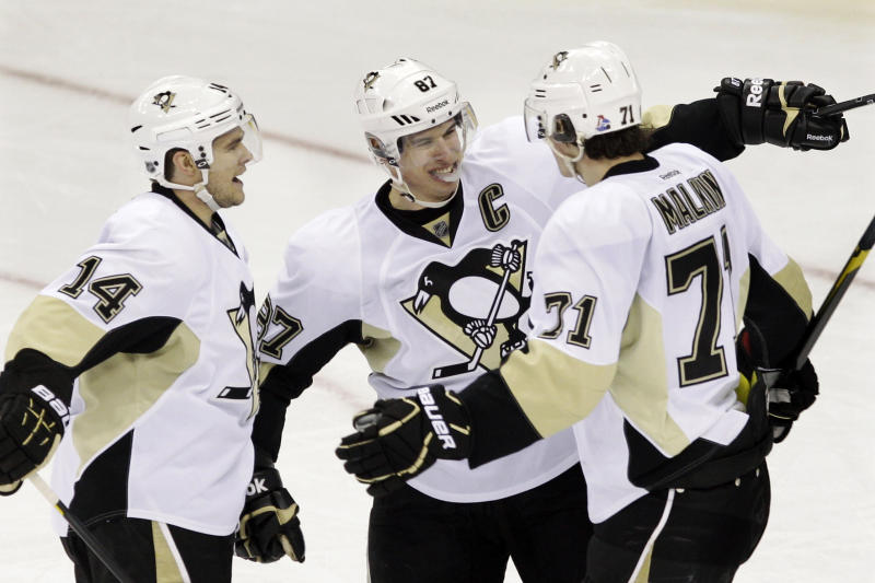 Pittsburgh Penguins' Chris Kunitz (14) and Sidney Crosby (87) celebrate a goal by Evgeni Malkin (71), of Russia, during the second period of an NHL hockey game in Newark, N.J., Saturday, March 17, 2012. Crosby got an assist on the play. (AP Photo/Mel Evans)
