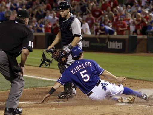 Texas Rangers' Ian Kinsler, bottom, scores on a Adrian Beltre single as home plate umpire Brian Runge, left, and New York Yankees catcher Russell Martin look on in the sixth inning of a baseball game on Wednesday, April 25, 2012, in Arlington, Texas. (AP Photo/Tony Gutierrez)