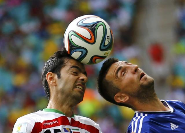 Iran's Pejman Montazeri (L) jumps for the ball with Bosnia's Vedad Ibisevic during their 2014 World Cup Group F soccer match at the Fonte Nova arena in Salvador June 25, 2014. REUTERS/Ivan Alvarado (BRAZIL - Tags: SOCCER SPORT WORLD CUP)
