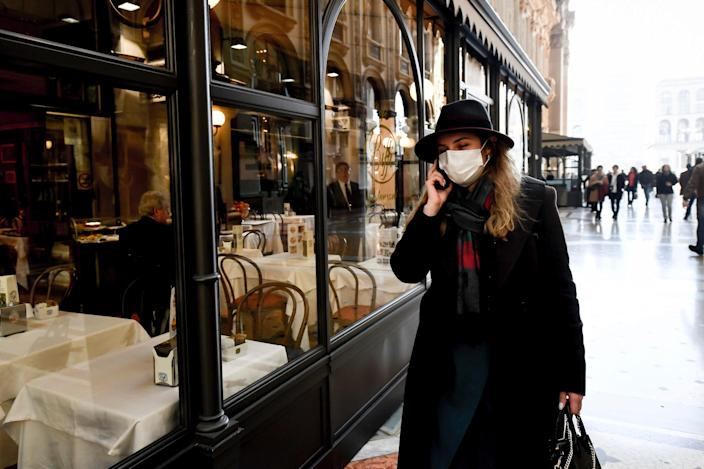 A woman wearing a sanitary mask talks on the phone as she walks in the Vittorio Emanuele Gallery shopping arcade, in downtown Milan, Italy, Monday, Feb. 24, 2020.