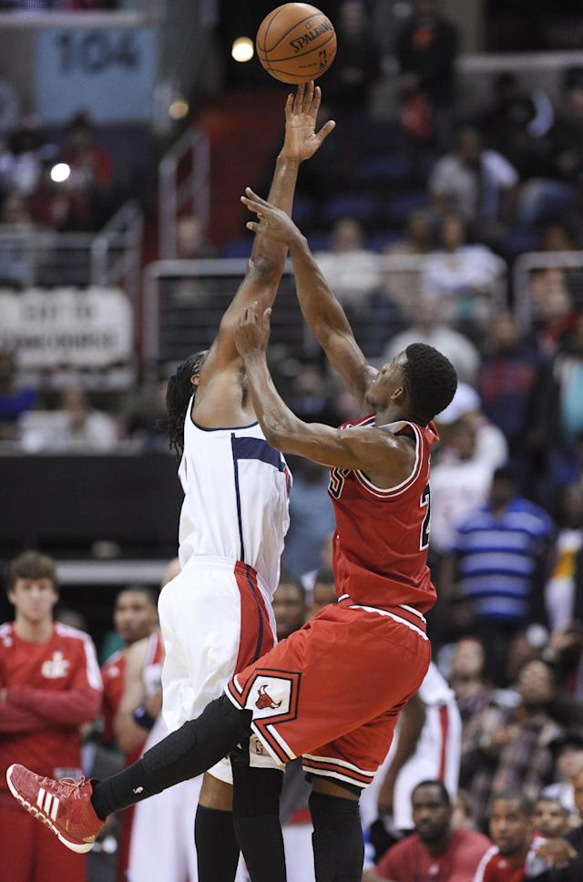 Washington Wizards forward Nene Hilario, left, blocks a shot at the end of the game from Chicago Bulls guard Jimmy Butler, right, in an NBA basketball game in Washington, Friday, Jan. 17, 2014. The Wizards won 96-93. (AP Photo/Susan Walsh)