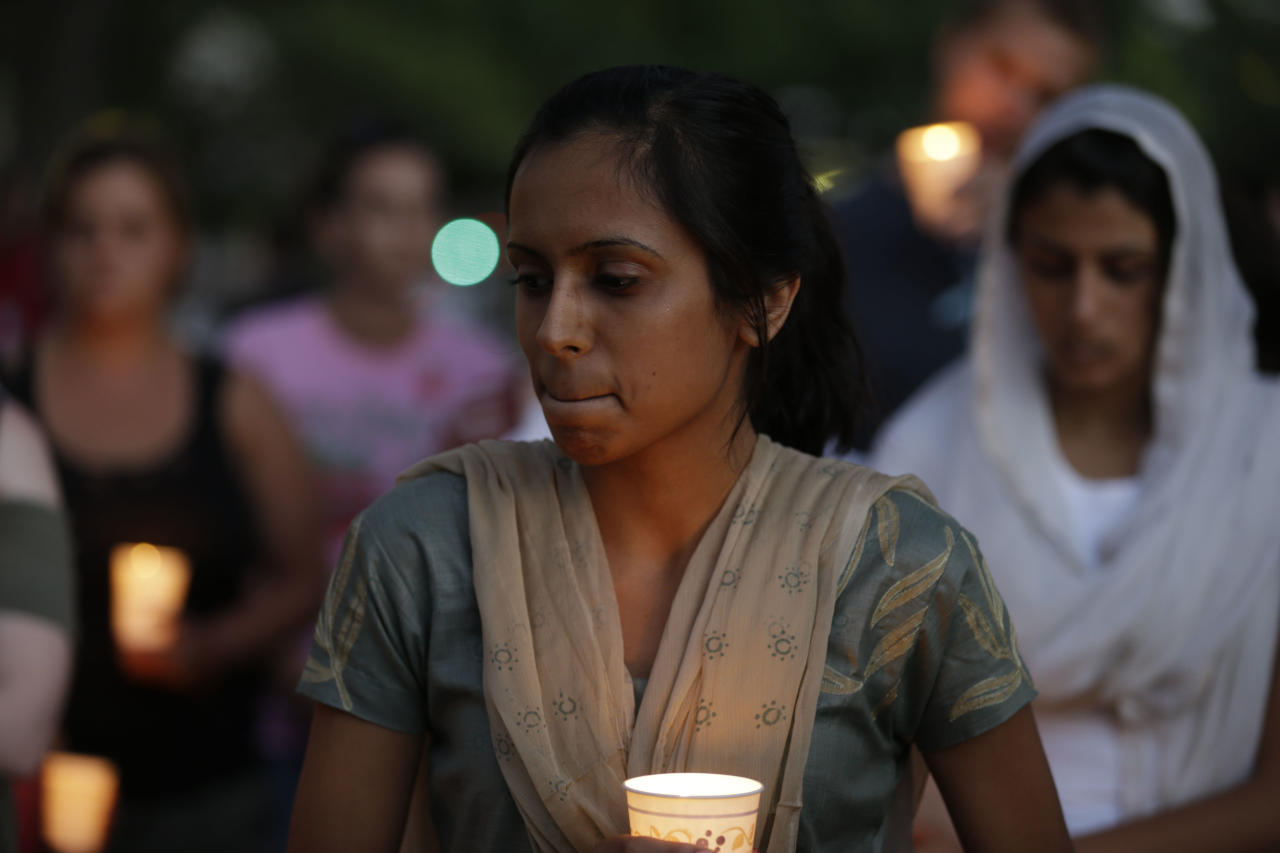 Mourners take part in a candle light vigil for the victims of the Sikh Temple of Wisconsin shooting, in Milwaukee, Sunday, Aug 5, 2012. An unidentified gunman killed six people at a Sikh temple in suburban Milwaukee on Sunday in a rampage that left terrified congregants hiding in closets and others texting friends outside for help. The suspect was killed outside the temple in a shootout with police officers. (AP Photo/Jeffrey Phelps)