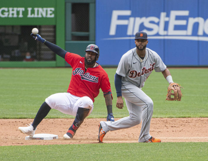 Cleveland Indians' Franmil Reyes is safe at second as the ball gets away from Detroit Tigers' Willi Castro during the sixth inning of a baseball game in Cleveland, Sunday, April 11, 2021. (AP Photo/Phil Long)