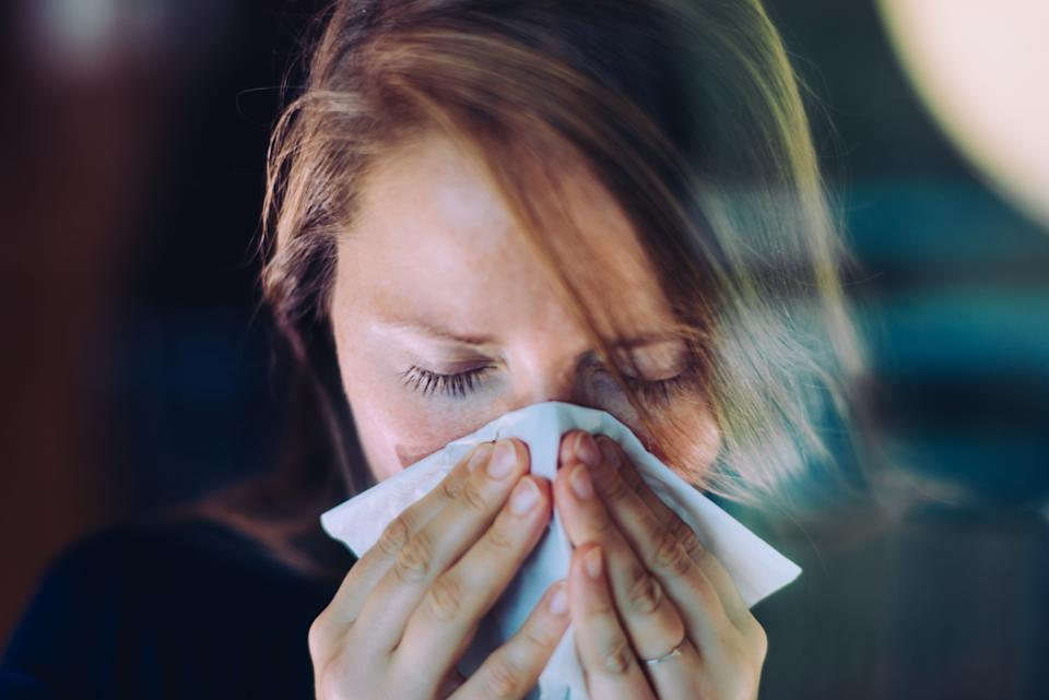 Woman sneezing behind a window, using a tissue.