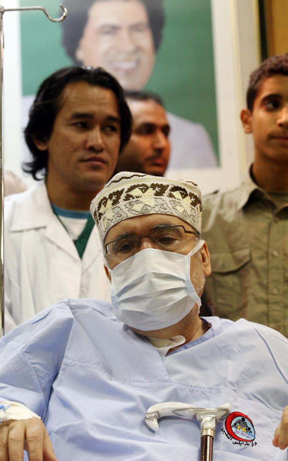 Abdelbaset Ali Mohmet al-Megrahi wears a medical mask as he sits on a wheelchair during a meeting with an African Delegation at a hospital in Tripoli on September 9, 2009 - MAHMUD TURKIA/AFP