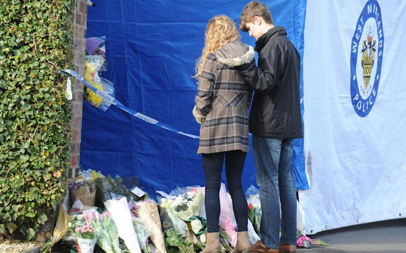 Lydia Wilkinson, the daughter of stabbing victims Peter and Tracey Wilkinson, views floral tributes at her family home in Stourbridge, West Midlands - Credit: PA