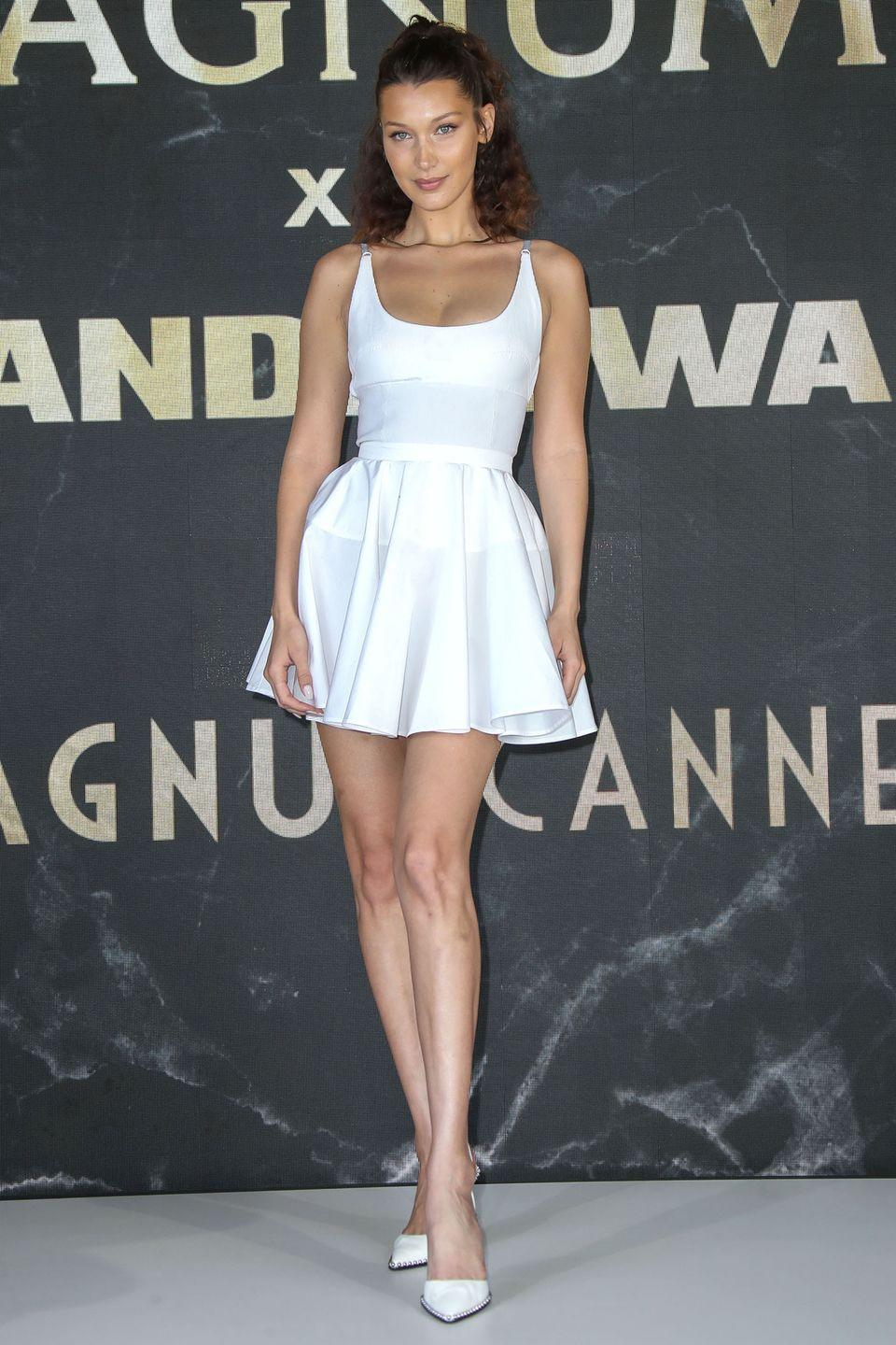"""<p>in white tennis-style mini dress with a deep scoop neckline at the Magnum press conference during the 71st <a href=""""https://www.harpersbazaar.com/celebrity/red-carpet-dresses/g20529068/cannes-2018-red-carpet/"""" rel=""""nofollow noopener"""" target=""""_blank"""" data-ylk=""""slk:Cannes Film Festival"""" class=""""link rapid-noclick-resp"""">Cannes Film Festival</a>.</p>"""