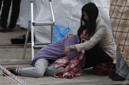 Relative of a missing passenger onboard the capsized Sewol ferry cries at a port in Jindo