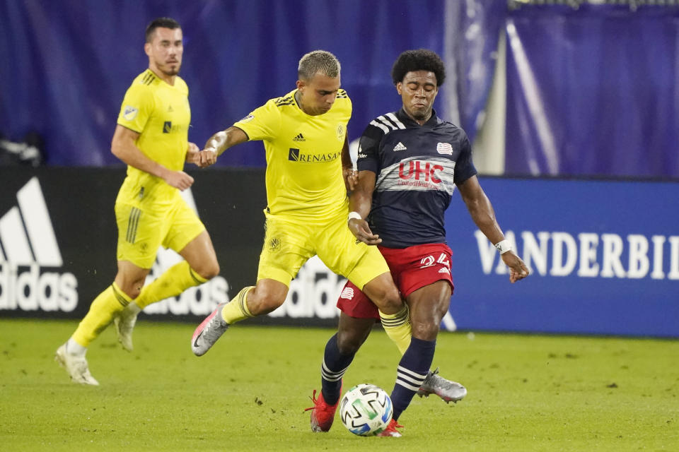 Nashville SC forward Randall Leal, center, and New England Revolution defender DeJuan Jones (24) battle for the ball during the first half of an MLS soccer match Friday, Oct. 23, 2020, in Nashville, Tenn. (AP Photo/Mark Humphrey)