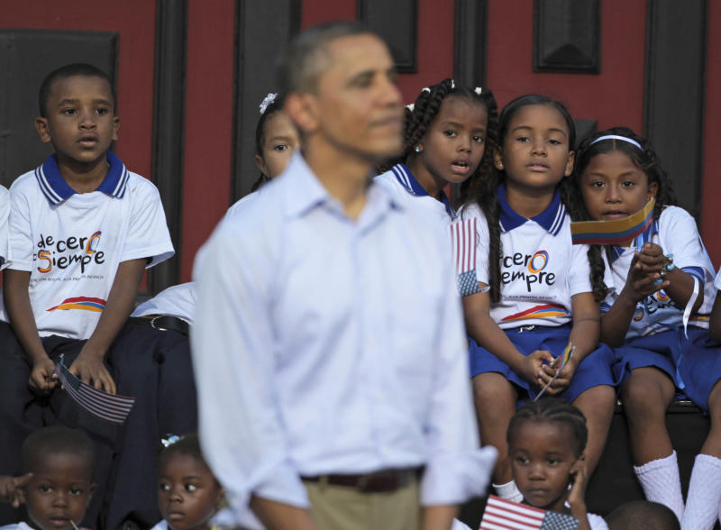 Colombian children look at President Barack Obama, foreground, during a land titling event for Afro-Colombian communities in Cartagena, Colombia, Sunday April 15, 2012. (AP Photo/Fernando Llano)