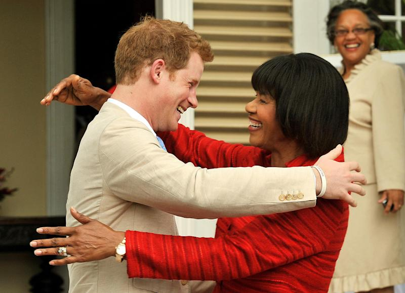 Prince Harry embraces the Prime Minister of Jamaica Portia Simpson Miller after he arrived at Devon Hall , in Jamaica as part of a Diamond Jubilee tour where he is a representating Queen Elizabeth II. (Photo by John Stillwell/PA Images via Getty Images)