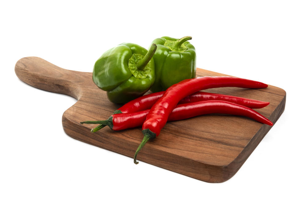 Wooden board of green bell and red chili peppers isolated on white background. High quality photo