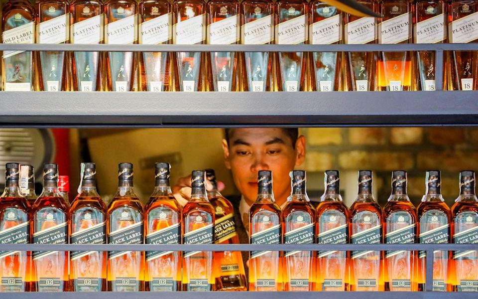 A bartender takes a bottle of Johnnie Walker whisky at Barmaglot bar in Almaty - SHAMIL ZHUMATOV/REUTERS