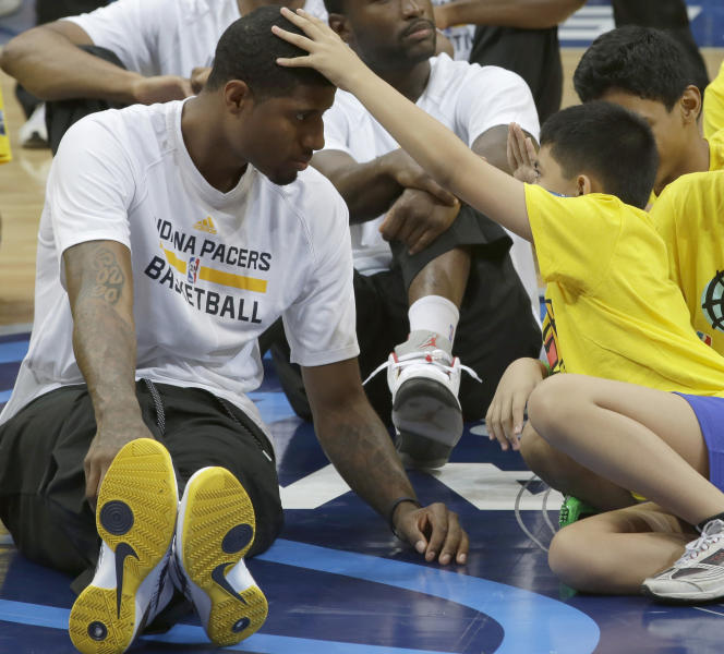 Indiana Pacers' Paul George gets a tap on the head by a Filipino Special Olympics athlete Wednesday, Oct. 9, 2013, during a basketball clinic at the Mall of Asia Arena in Pasay city, south of Manila, Philippines. The Indiana Pacers will play against the Houston Rockets on Thursday in the first NBA game in this basketball-obsessed Southeast Asian nation, part of the NBA's global schedule that will have eight teams play in six countries this month.(AP Photo/Bullit Marquez)