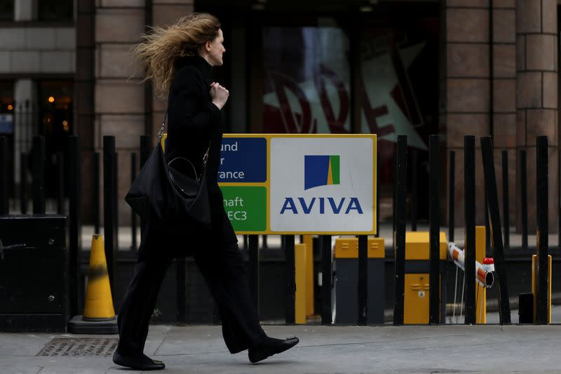 FILE PHOTO: A pedestrian walks past the Aviva logo outside the company head office in the city of London