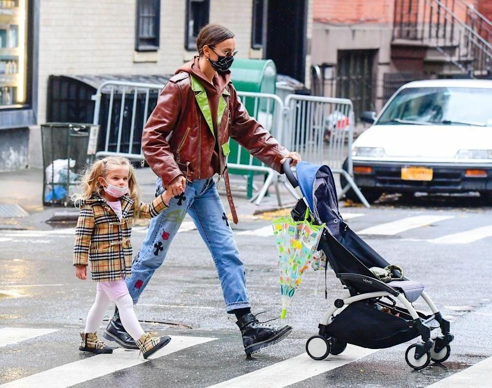 <p>Holding her's and ex-partner Bradley Cooper's daughter's hand, Shayk looked fierce in lace-up boots, medium-wash jeans, and a brown biker jacket with green accents.</p>