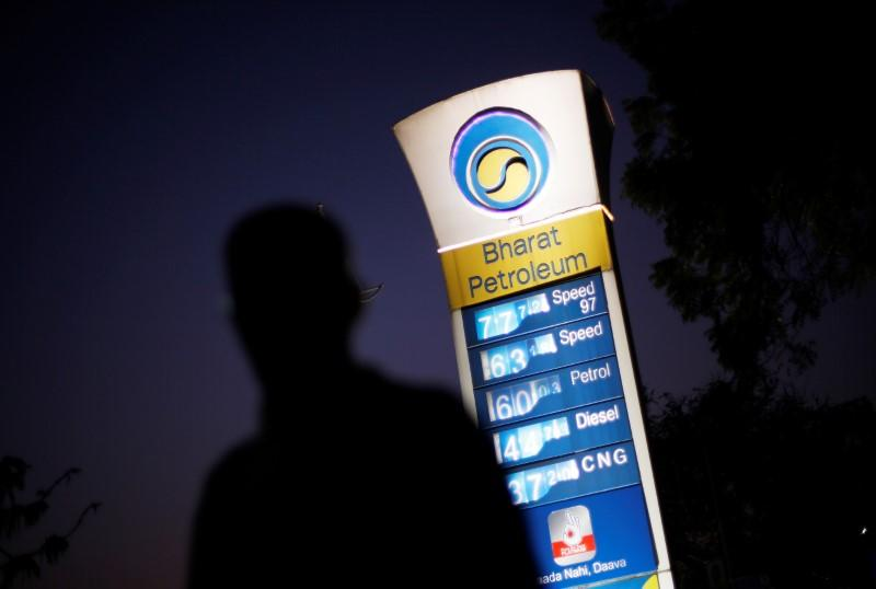 FILE PHOTO: A Bharat Petroleum oil pump station displays the price of unleaded petrol and Diesel as a pedestrian walks past in New Delhi