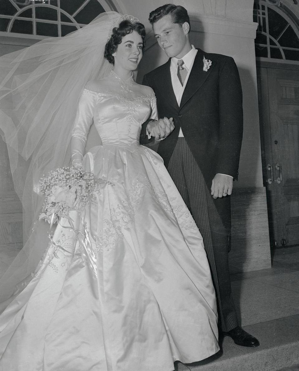 """<p>The same year that Elizabeth Taylor starred in <em>Father of the Bride</em>, the starlet wed hotel heir Conrad """"Nicky"""" Hilton. The bill for the elegant nuptials in Beverly Hills was paid for by MGM Studios and the actress's dress was designed by the studio's costume designer, <a href=""""https://www.brides.com/story/elizabeth-taylor-wedding-day-photos"""" rel=""""nofollow noopener"""" target=""""_blank"""" data-ylk=""""slk:Helen Rose"""" class=""""link rapid-noclick-resp"""">Helen Rose</a>. </p>"""