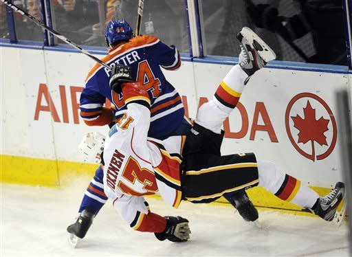 Edmonton Oilers' Corey Potter, rear, checks Calgary Flames' Oli Jokinen during the second period of an NHL hockey game in Edmonton, Alberta, on Friday, March 16, 2012. (AP Photo/The Canadian Press, John Ulan)