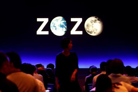 FILE PHOTO: A woman is seen in front of a sign reading Zozo, which operates Japan's popular fashion shopping site Zozotown, at an event in Tokyo launching the debut of its formal apparel items