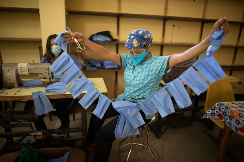 A worker of the state-owned Concepcion Palacios Maternity Hospital manufactures face masks in Caracas, Venezuela, March 17, 2020. Workers of the city's main maternity are preparing makeshift masks with disposable blue sheets to distribute to medical staff and other workers of the health center for protection of an eventual spread of the COVID-19 illness.