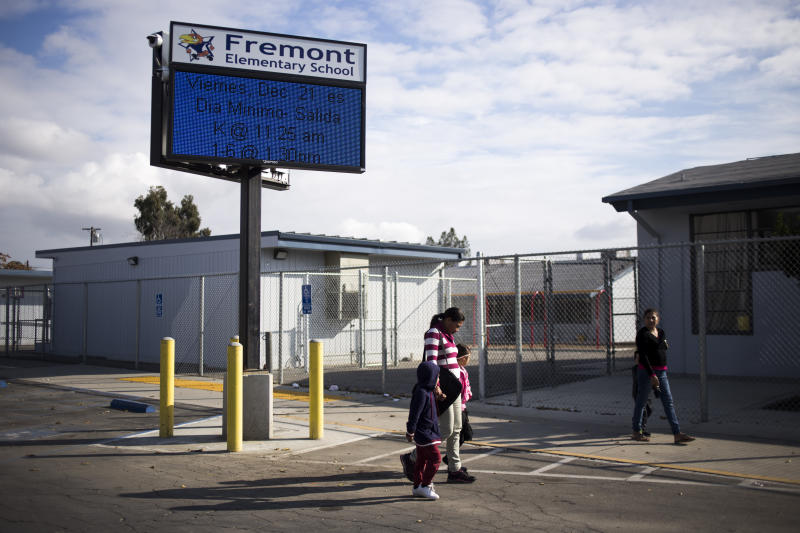 BAKERSFIELD, CA - DECEMBER 18, 2018: Nubia Estrada Umanzor, 34, holds hands with her children as they walk to Fremont Elementary School in Bakersfield, CA., on Monday, Dec. 18, 2018. (Jenna Schoenefeld for The Washington Post via Getty Images)