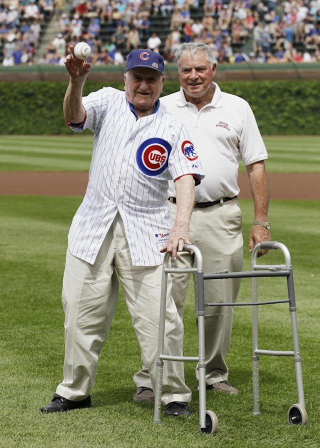 Former Chicago Cubs shortstop Lennie Merullo, left, throws out a ceremonial first pitch as his son Lennie Merullo Jr., looks on before a baseball game between the Miami Marlins and the Chicago Cubs in Chicago, Saturday, June 7, 2014. Lennie Merullo is the only living Cubs player to have played in a World Series. (AP Photo/Nam Y. Huh)