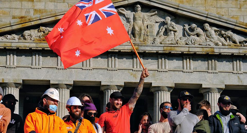 Men standing outside the shrine of remembrance in Melbourne wearing hi-vis and no masks protesting.