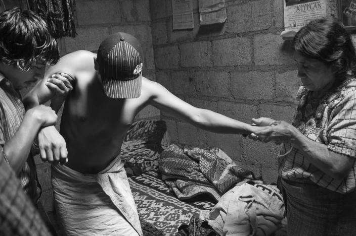 <p>With the aid of his mother and a friend, Pedro Mendoza attempts to walk after a healing. (Photograph by Fran Antmann) </p>