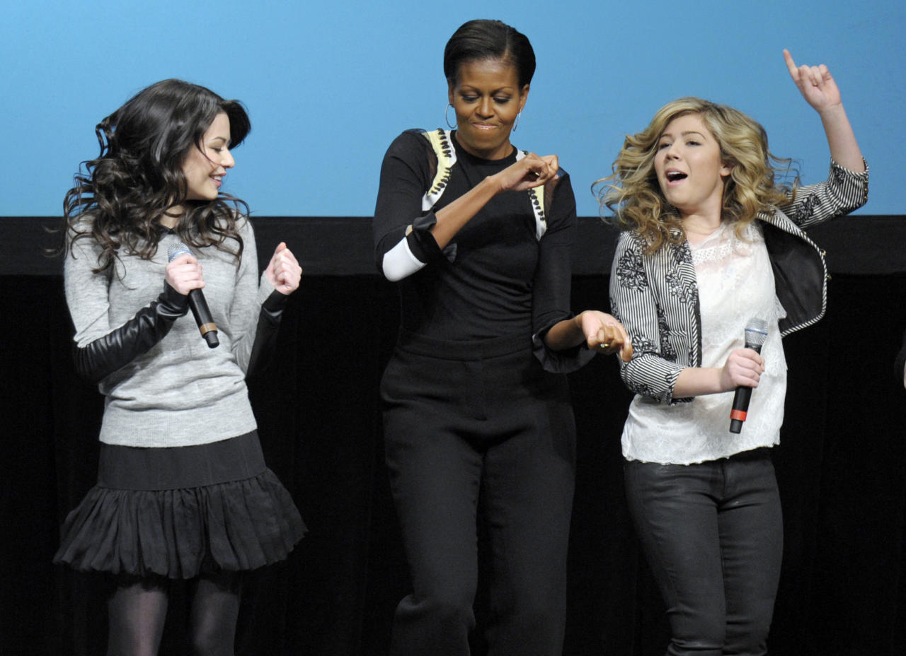 "First lady Michelle Obama joins cast members Miranda Cosgrove, left, and Jennette McCurdy, right of Nickelodeon's iCarly in performing the 'random dance' at a special screening of ""iMeet The First Lady"" episode of the show, Friday, Jan. 13, 2012, at Hayfield Secondary School in Fairfax, Va. (AP Photo/Cliff Owen)"