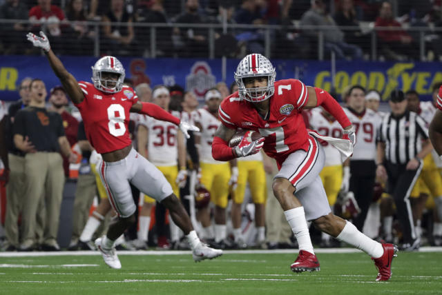 "Ohio State safety <a class=""link rapid-noclick-resp"" href=""/ncaaf/players/243237/"" data-ylk=""slk:Damon Webb"">Damon Webb</a> (7) runs an interception in for a touchdown in front of cornerback <a class=""link rapid-noclick-resp"" href=""/ncaaf/players/257060/"" data-ylk=""slk:Kendall Sheffield"">Kendall Sheffield</a> (8) during the first half of the Cotton Bowl NCAA college football game against Southern California in Arlington, Texas, Friday, Dec. 29, 2017. (AP Photo/LM Otero)"