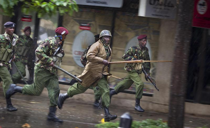 Kenyan police with clubs chase a small group of supporters of presidential candidate Raila Odinga after they ran down a street smashing shop windows in protest at the verdict of the Supreme Court in Nairobi, Kenya Saturday, March 30, 2013. Kenya's Supreme Court on Saturday upheld the election of Uhuru Kenyatta as the country's next president, in a verdict on a petition by candidate Raila Odinga appealing the election result, ending an election season that riveted the nation amid fears of a repeat of the 2007-08 postelection violence. (AP Photo/Ben Curtis)
