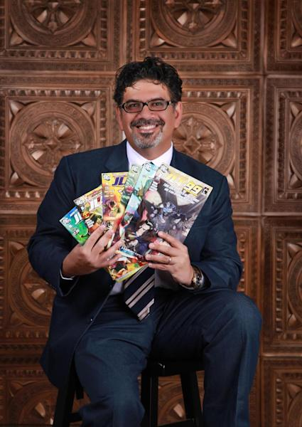 """In this image released by Teshkeel Media Group, comic book author Naif Al-Mutawa holds up copies of his comic book series """"The 99,"""" on Long Island, N.Y. (AP Photo/Teshkeel Media Group, Cara Hromada Photography)"""