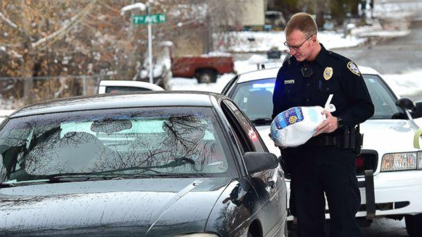 PHOTO: Billings, Montona police officer Eric Schnelbach gives a frozen turkey and a warning to Larry Riddle and his daughter Amber after they were pulled over for a minor traffic violation. Billings businessman Steve Goutanis donated the turkeys. (Larry Mayer, Billings Gazette)
