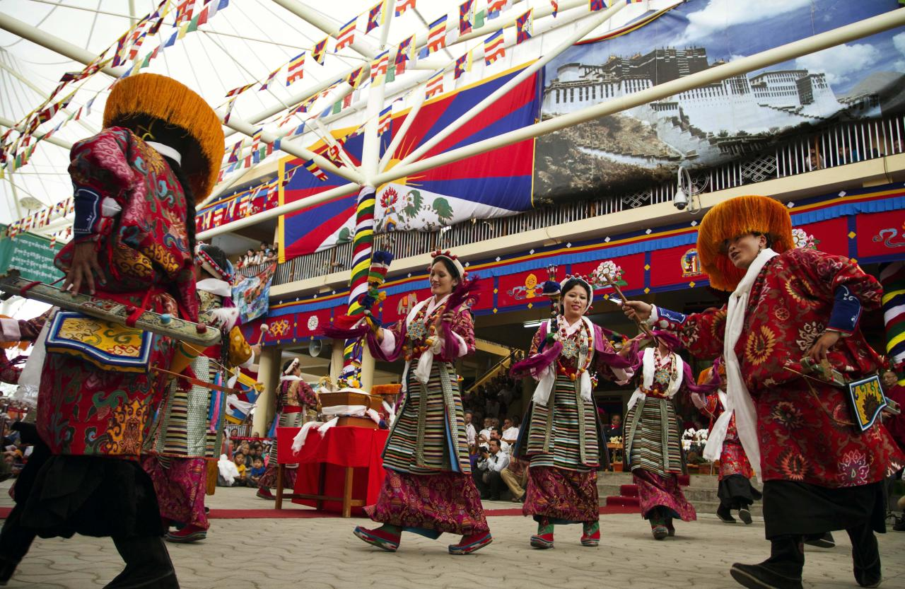 Tibetans in traditional costumes perform a dance at Tsuglakhang temple in Dharmsala, India, Friday, July 6, 2012. The Dalai Lama celebrates his 77th birthday with festivities held for the entire day at the temple's complex. (AP Photo/Ashwini Bhatia)