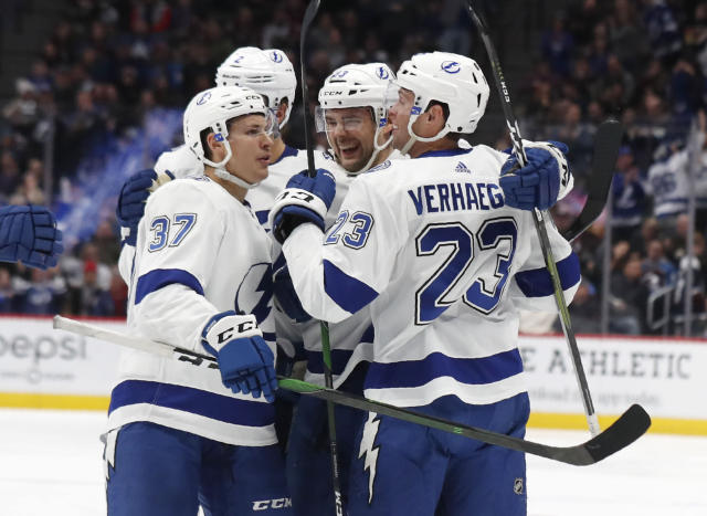 Tampa Bay Lightning defenseman Cameron Gaunce, third from left, is congratulated after his goal by, from left, center Yanni Gourde, defenseman Luke Schenn and center Carter Verhaeghe in the second period of an NHL hockey game against the Colorado Avalanche Monday, Feb. 17, 2020, in Denver. (AP Photo/David Zalubowski)