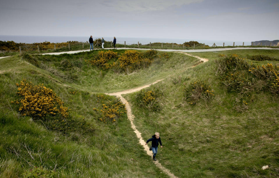 In this May 1, 2019, photo, a young boy runs down a path going through a World War II bomb crater at Pointe du Hoc, overlooking Omaha Beach, in Saint-Pierre-du-Mont, Normandy, France. On June 6, 1944, U.S. Rangers scaled the high coastal cliffs to capture a German gun battery. (AP Photo/Virginia Mayo)