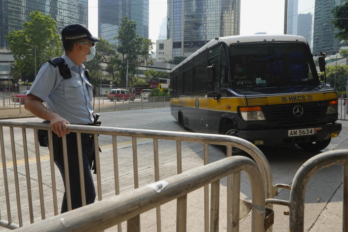 """A prison van, right, which a police officer says is carrying Tong Ying-kit arrives at a court in Hong Kong Tuesday, July 27, 2021. Hong Kong High Court will deliver verdict in the afternoon for the first person charged under Hong Kong's National Security Law. Tong was arrested in July 2020 after driving his motorbike into a group of police officers while carrying a flag bearing the protest slogan """"Liberate Hong Kong."""" He was charged with inciting separatism and terrorism. (AP Photo/Vincent Yu)"""