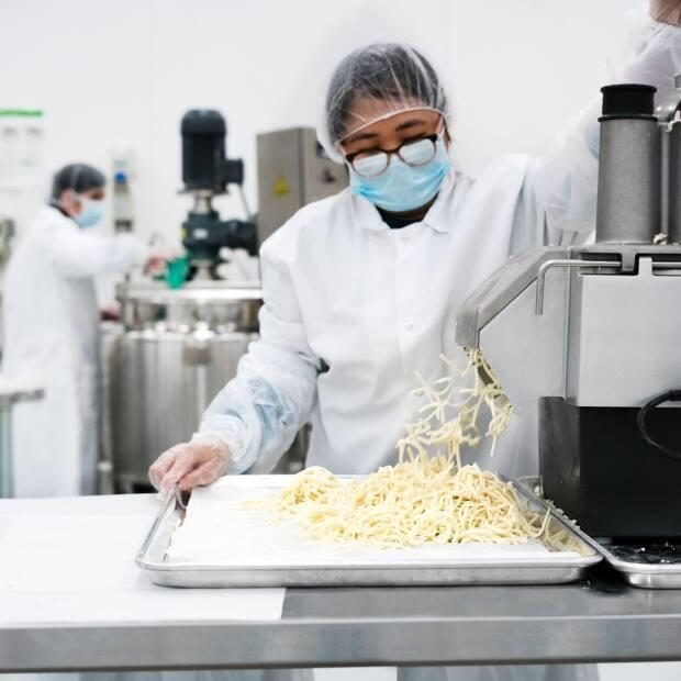 Employees at Nabati Foods making cheese in the new manufacturing facility in Edmonton. (Submitted by Nabati Foods - image credit)