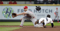 The helmet of Seattle Mariners' Mallex Smith, right, takes flight as he steals second base as St. Louis Cardinals shortstop Paul DeJong reaches for the throw during the third inning of a baseball game Wednesday, July 3, 2019, in Seattle. (AP Photo/Elaine Thompson)