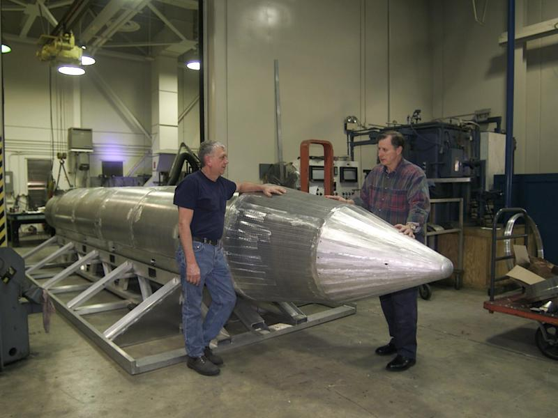 Al Weimorts, the creator of the GBU-43/B Massive Ordnance Air Blast bomb, and Joseph Fellenz, lead model maker, look over the prototype of the bomb before it was painted and tested in March 2003: Rex