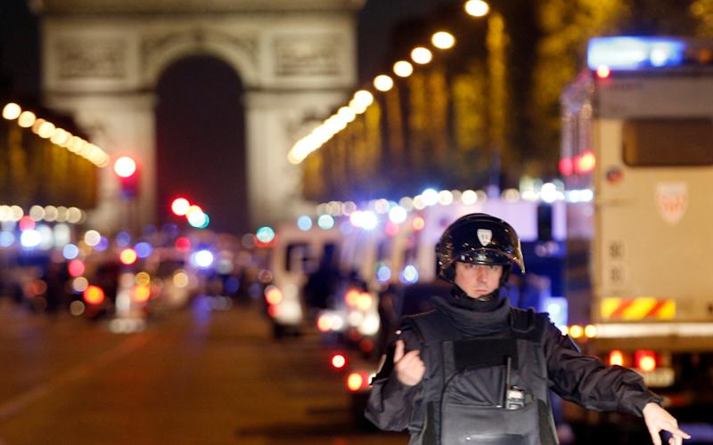A police officer stands guard after a fatal shooting in which a police officer was killed along with an attacker on the Champs Elysees in Paris - Credit: AP