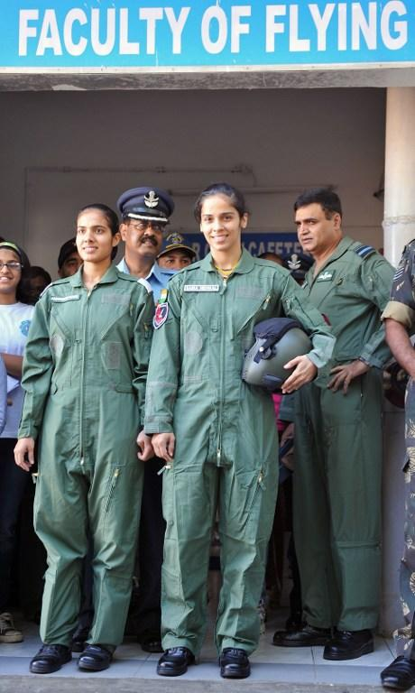 Indian badminton player Saina Nehwal (C), clad in a flight suit, poses with Indian Air Force personnel before her flight on a Kiran MK-1 trainer aircraft at Air Force Academy Dundigal, in the outskirts of Hyderabad, on September 28, 2012. Nehwal, who flew on an Air Force trainer aircraft, was a special guest at the academy for the closing ceremony of the Inter Squadron Sports championship. AFP PHOTO / Noah SEELAM